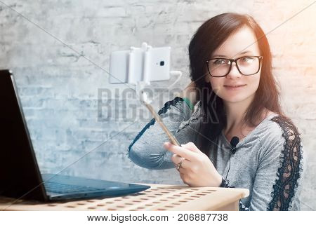 The girl with the glasses is a live broadcast from a mobile phone, Female blogger shoot video using the camera of your smartphone,