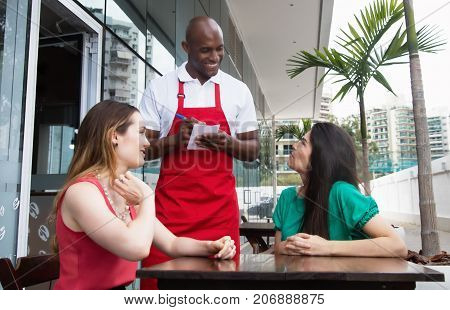 Friendly african american waiter with guests in restaurant