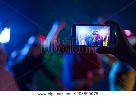 Right hand holding smartphone camera snap shot photo memories people christmas party celebrating bancing together group in midnight club Live social online concept.