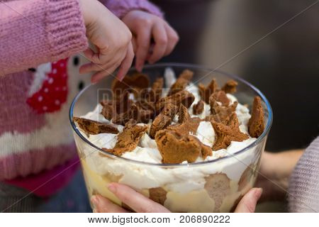child and mother sprinkle biscuit over an authentic homemade family christmas gingerbread custard trifle