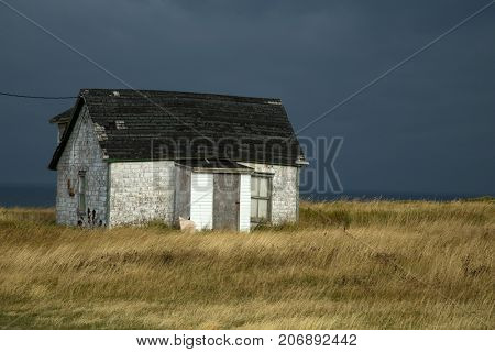 Old fisherman house with tiles in a dark grey sky in iles de la madeleine in Canada
