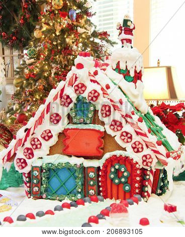 Beautiful homemade Christmas gingerbread house with holiday decorations in the background.