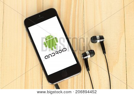 Kiev Ukraine - May 22 2015: iPhone with Android logotype on its screen and headphones on wooden background