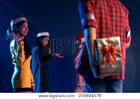 Young handsome man asian hidden gift box for giving girlfriend in christmas party celebrating new year midnight at club Closeup woman