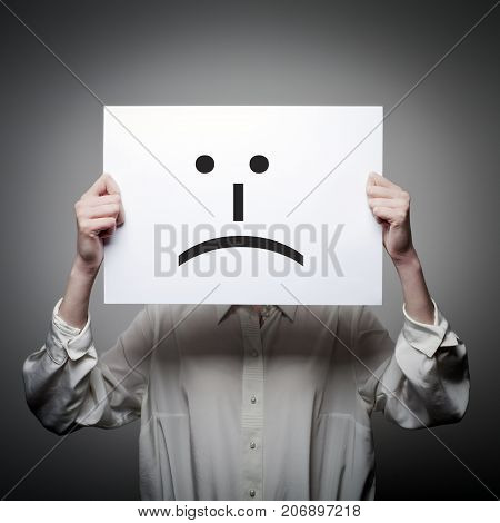 Woman is holding white paper with smile. Unhappy and trouble concept.
