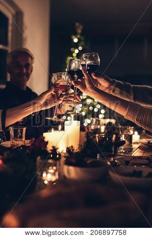 Close up shot of family toasting wine at christmas dinner. Family enjoying christmas dinner together at home with focus on hands and wine glasses.