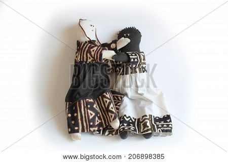 White doll with hand over the mouth of black doll concept silencing, racial minority, dominance, isolated on white
