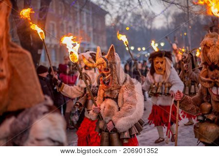 PERNIK, BULGARIA - JANUARY 27, 2017: Masked participant in scary fur costume is holding burning torch while marching at Surva, the International Festival of the Masquerade Games