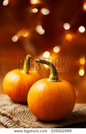 Autumn Pumpkin Happy Thanksgiving Background with orange pumpkins on wooden table with copyspace and bokeh abstract lights