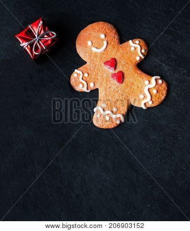 Christmas composition with Christmas gift Gingerbread man cookie fir tree branches xmas holiday decorations and festive symbols on dark background with copy space for your design or Happy New Year text