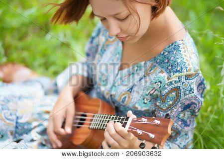 Young Woman Playing On Ukulele