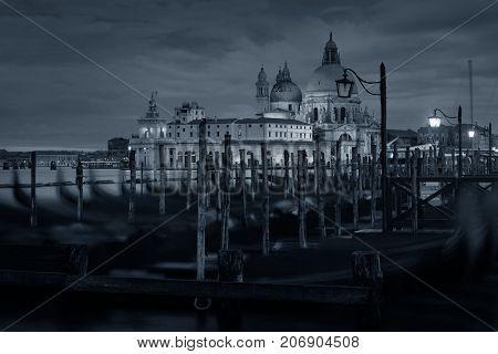 Venice church  Church Santa Maria della Salute and gondola park at water front. Italy.