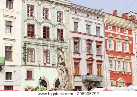Part of a buildings facades of west side of Rynok Square with Neptune sculpture on foreground in Lviv Ukraine