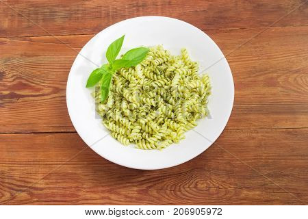 Top view of the white dish with cooked spiral pasta with sauce pesto decorated with basil twig on a surface of old wooden planks