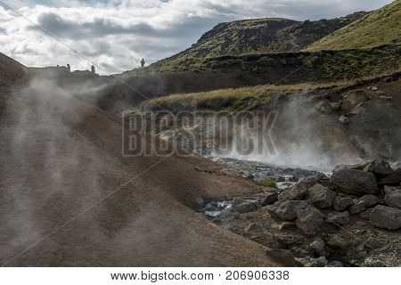 Geothermal area in Iceland. Multicolored ground and steam in foreground. Sky green hills and people silhouettes in background.