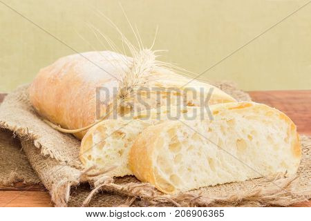 Two slices and half of loaf of the ciabatta with wheat ear on a sackcloth