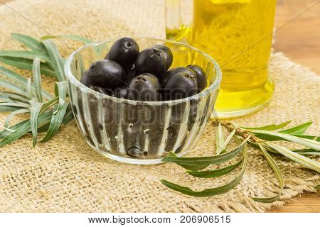 Canned black olives in small glass bowl closeup on a sackcloth on a background of olive branches and bottle of olive oil