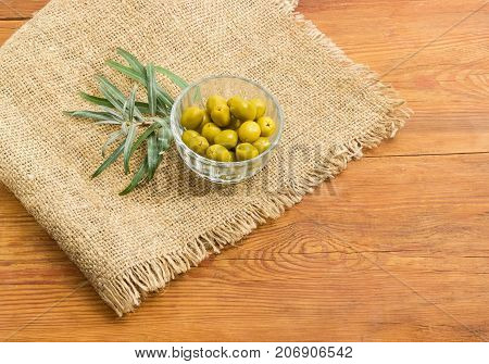 Canned green olives in small glass bowl and olive branch on a sackcloth on a surface of an old wooden planks