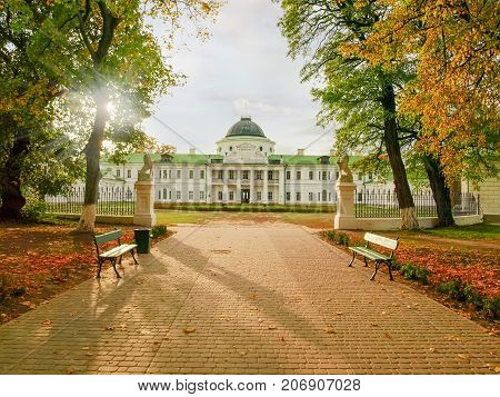 End of alley in the autumn park and 18th century neoclassical palace in national historic cultural preserve Kachanivka Ukraine