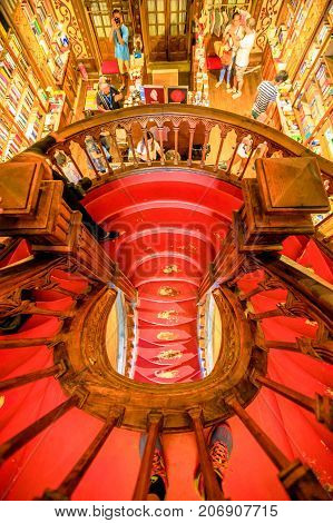 Oporto, Portugal - August 13, 2017: aerial view of Library Lello and Irmao, one of the world's most beautiful libraries in Porto, known for Harry Potter, from large spiral staircase with red steps