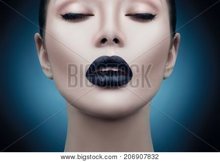 High Fashion Model Girl Portrait with Trendy gothic Black Make up, dark portrait. Halloween Vampire Woman with black matte lips over deep blue background. model girl face with black lipstick makeup