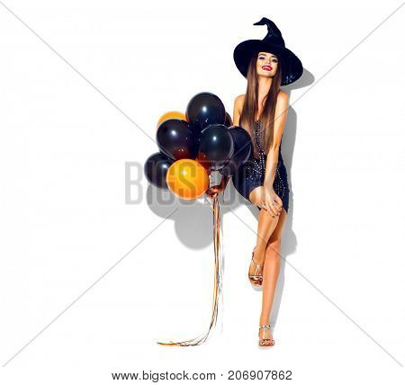Halloween Party girl. Happy Halloween Sexy Witch with Air balloons. Beautiful young surprised woman in witches hat and short dress holding black and orange air balloons. Isolated on white background