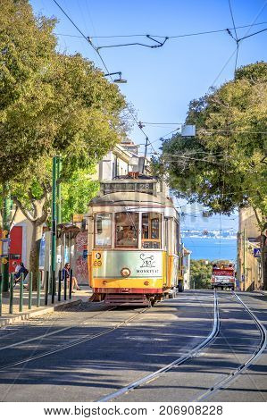 Lisbon, Portugal - August 25, 2017: famous historic yellow Tram 28 on Alfama districts street. Scenic Tagus river on background. Trams are icon of the Portuguese capital. Lisbon urban views.