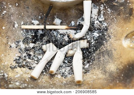 Cigarettes in an ashtray . Photos in the studio