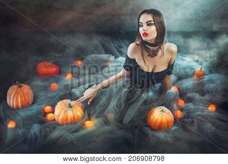 Halloween Witch with Pumpkins and magic lights in a dark room. Beautiful young sexy woman in witches costume sitting with pumpkins and candles. Witchcraft scene art design Halloween party art design