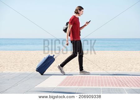Full Body Portrait Of Smiling Man Walking By Sea With Suitcase And Cellphone