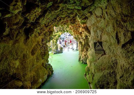 Sintra, Portugal - August 9, 2017: caves that lead to the popular Waterfall Lake in the gardens of Quinta da Regaleira or Regaleira Palace, famous landmark and Unesco Heritage in the center of city.