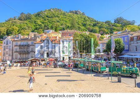 Sintra, Portugal - August 8, 2017: beautiful view of Castle of the Moors on top of a hill above Sintra from Amelia Square and Green Tourist Train in Historic Center, Unesco World Heritage Site.