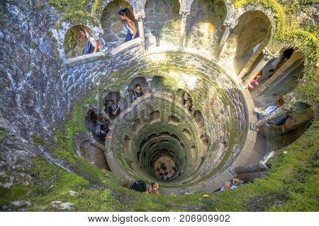 Sintra, Portugal - August 9, 2017: tourists inside the iconic Initiation well a masonic underground passage in Quinta da Regaleira.World Heritage Site by Unesco within the Cultural Landscape of Sintra