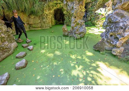 Sintra, Portugal - August 9, 2017: tourist woman crossing the Waterfall Lake within the garden of Quinta da Regaleira or Regaleira Palace, famous landmark and Unesco Heritage in the center of the city