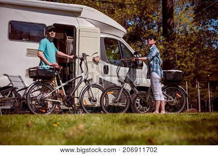 Woman with a man on electric bike resting at the campsite. Family vacation travel, holiday trip in motorhome, Caravan car Vacation.