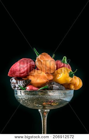 different kinds of hot chili peppers on silverware on black background copyspace