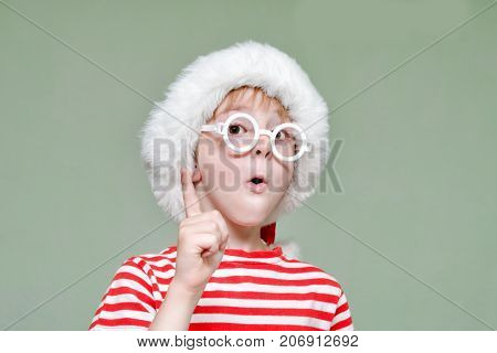 Boy With Glasses And A Santa Hat Is Threatening With His Finger. Portrait