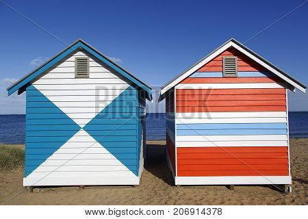 Two colorful beach boxes on Melbourne's famous Brighton Beach in Australia with a blue sky and ocean background
