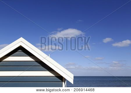 One of the colorful beach huts on Melbourne's Brighton Beach, Australia with a vibrant summer blue sky and ocean background.