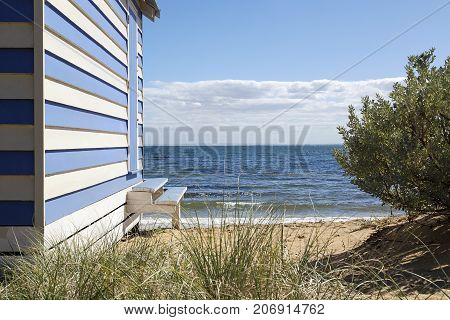 Striped beach hut in the dunes on Brighton Beach in Melbourne with a blue sky and ocean background