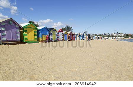 Brighton Beach, Australia: March 31, 2017: The colorful beach huts on Brighton Beach in Melbourne. Unidentified people walk down the beach.