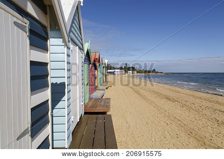 Row beach huts on Melbourne's Brighton Beach with a blue sky and ocean background
