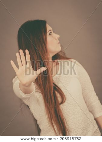Angry apodicticity woman showing stop sign gesture with open hand denying something