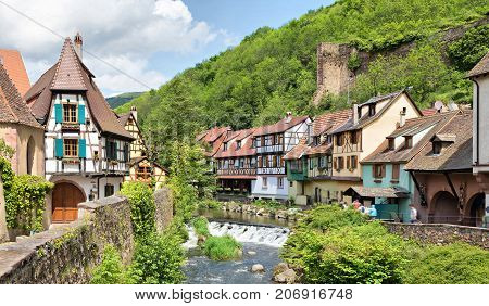 French traditional half-timbered houses and La Weiss river in Kayserberg village in Alsace France