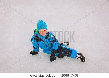 cute happy boy learning to skate, play hockey in winter