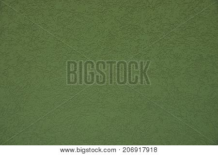 Green background from a fragment of a concrete wall of a building