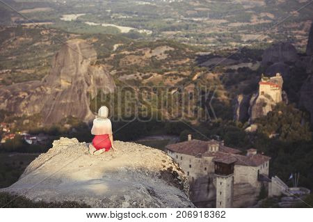 Alone girl in a red dress and scarf sits on the edge of the rock and prays at the monasteries of Meteora. Female on the rock and monasteries of Meteora in Greece in Thessaly