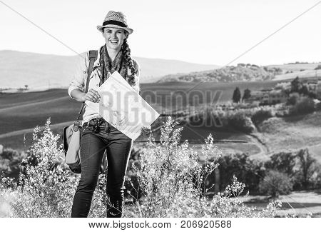 Discovering magical views of Tuscany. happy healthy woman hiker with bag hiking in Tuscany with map