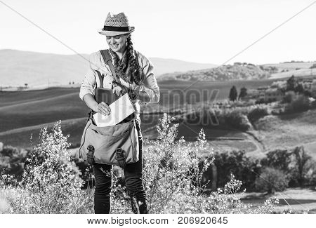 Discovering magical views of Tuscany. adventure woman hiker in hat with bag enjoying Tuscany view taking map