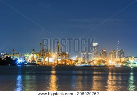 Commercial docks with light at night with a ship and cranes